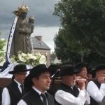 Männer in traditionellen bretonischen Trachten, alle mit dem typischen schwarzen Hut mit Samtband tragen die Statue der schwarzen Muttergottes von Le Folgoet an den Zuschauern und Pilgern vorbei.