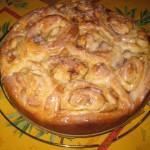 Kuchen aus Apfel-Zimtschnecken mit Puderzuckerguss kühlt auf einem Kuchengitter aus.