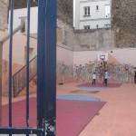 Auf dem Bild ist ein Bolzplatz zu sehen, der in einem betonierten Hinterhof angelegt wurde und dessen Mauern mit bunten Bildern bemalt sind.