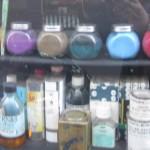 Das Bild zeigt das Schaufenster eines Malerladens in Paris, ion dessen Regalen Gläser mit bunten Farben stehen.