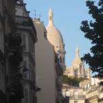 Das Bild zeigt den Blick auf die Pariser Kirche Sacré Coeur, fotografiert durch eine Straßenschlucht im 9. Arrondissement.