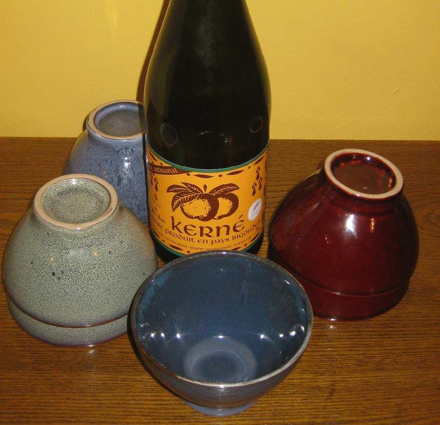 Blaue Bolée de Cidre mit andersfarbigen Cidretassen und einer Flasche Cidre.