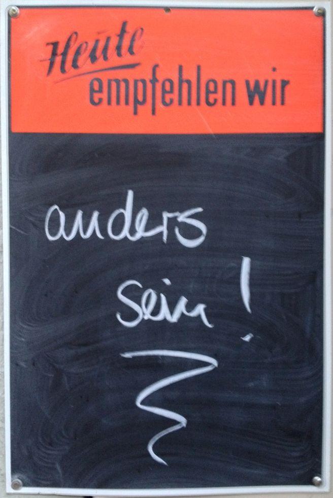Das Bild zeigt eine Schiefertafel eines Cafés. darauf steht: Heute empfehlen wir: anders sein!