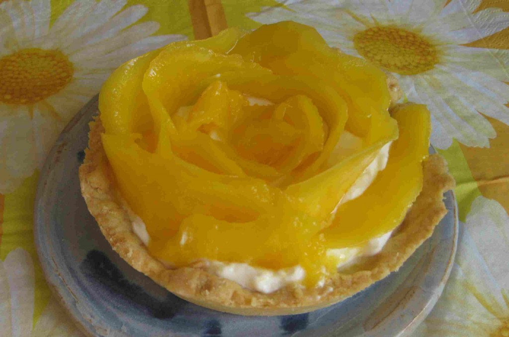 Foto eines Mangotartletts, bei dem die Mangostreifen wie eine Rose angeordnet wurden.