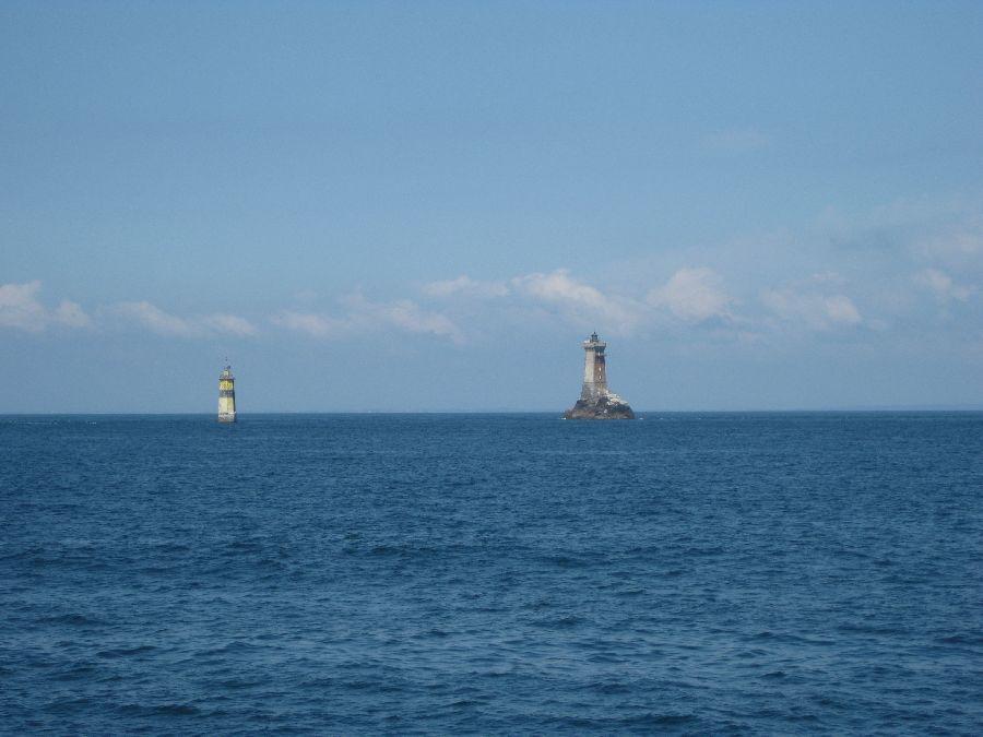 Das Foto zeigt einen kleinen Leuchtturm und eine Boje vor der bretonischen Küste, bei ruhigem Seegang und Sonnenschein.