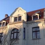 Das Foto zeigt ein altes Kölner Haus mit Stuckverzierungen am weiß getünchten Giebel in der Morgensonne.