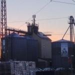 Hinter einem Industriegbäude mit zwei großen Tanks geht die Sonne auf und der Himmel färbt sich rosa-orange-gelb-violett