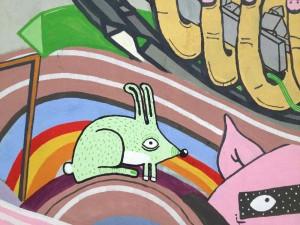 Das Bild zeigt eine Hauswand, auf die ein grünes Fabeltier mit Fühlern gemalt wurde.