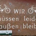 Das Foto zeiogt ein Schild auf dem steht: Wir müssen leider draußen bleiben. Daneben sind zwei Fahrräder abgebildet.