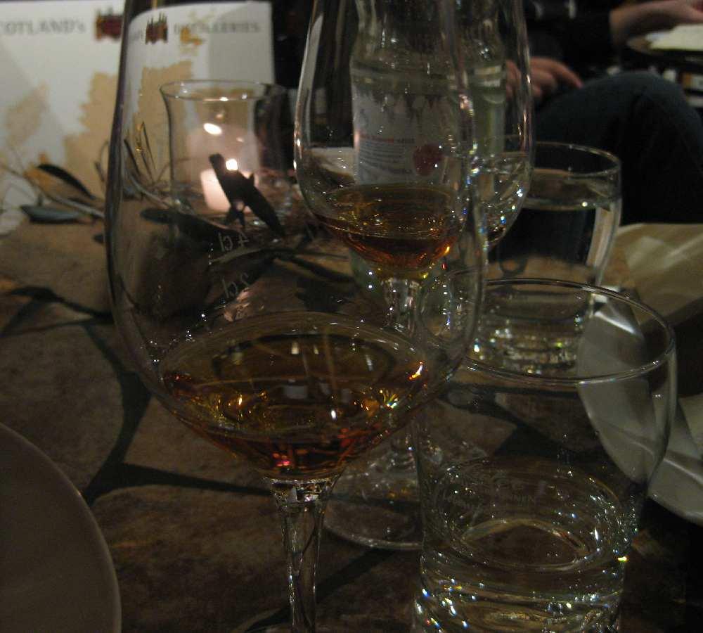 Das Foto zeigt ein Glas, in dem ein Dram Whisky eingeschenkt ist auf einem kleinen Bistrotisch im Keller des Weinhaus am Brunnen.