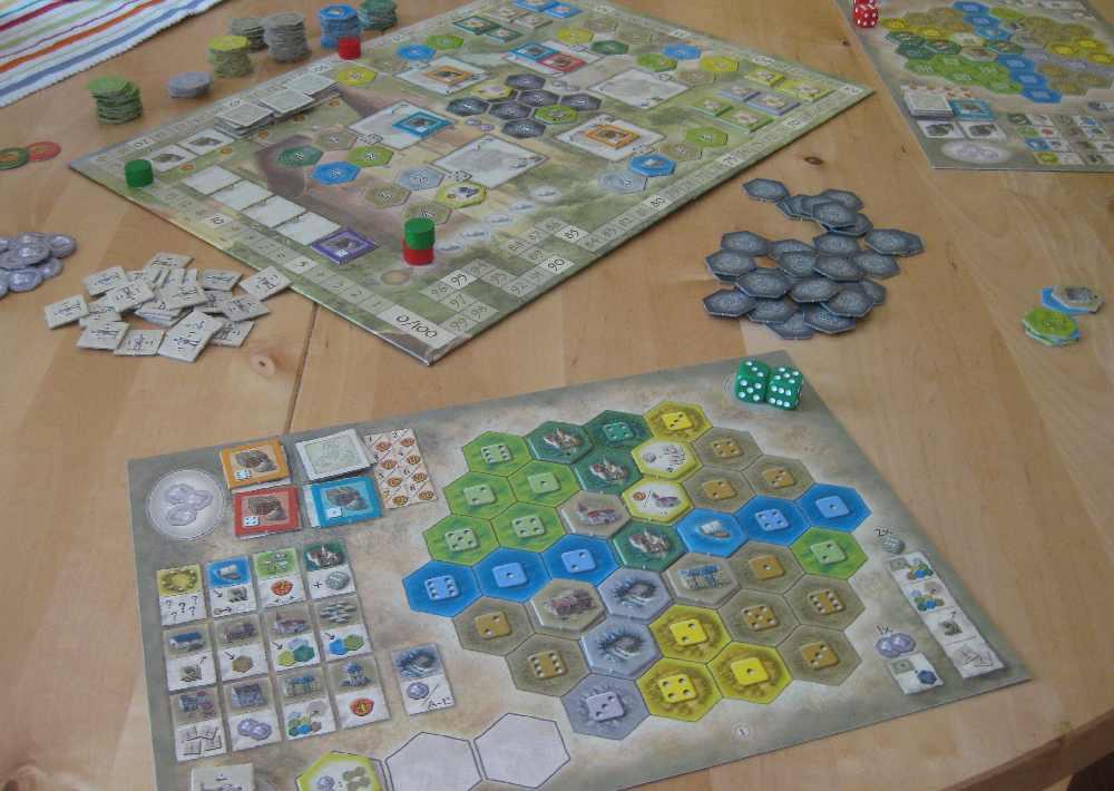 Spielpläne des Spiels Burgen von Burgund mit einigen Plättchen, die bereits ausgelegt wurden.