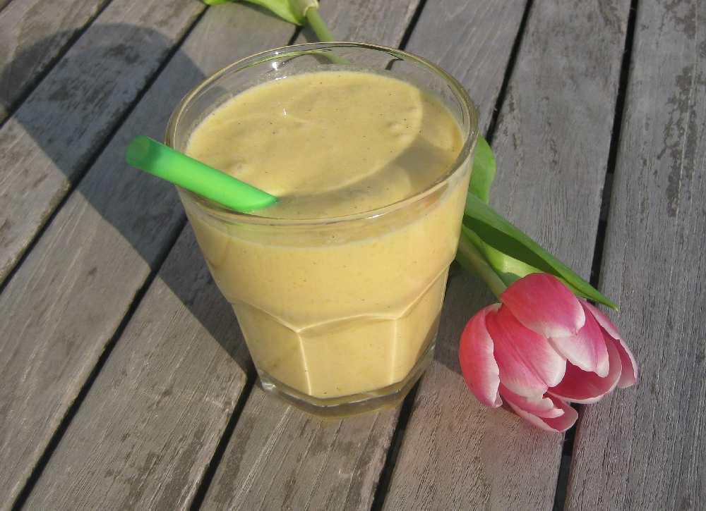 Der mango-gelb glänzende Shake zusammen mit einem grünen Strohhalm in einem Glas auf einem Holztisch, auf den die Abendsonne scheint, mit einer rosa Tulpe daneben.