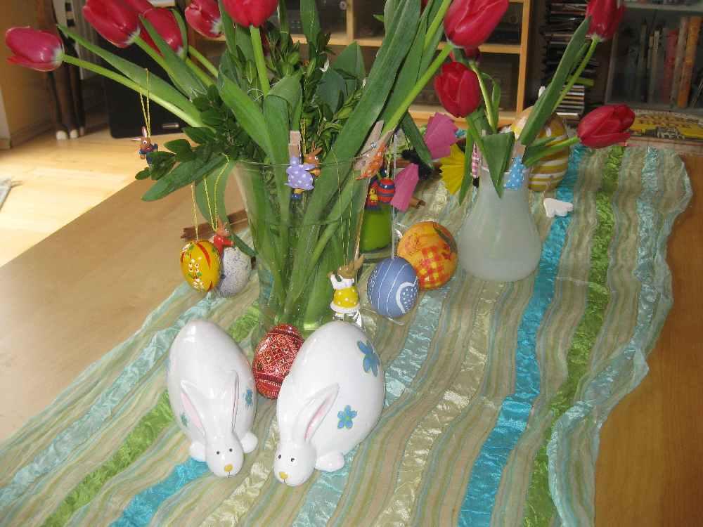 Foto eines Tischs, der mit roten Tulpen, bunte bemalten Ostereiern und Porzellanhasen dekoriert ist.