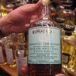 Eine Hand hält die Flasche mit dem Etikett in die Kamera