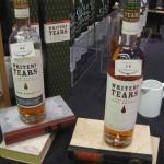 Die Flaschen des Writer's tears stehen auf übereinandergeschichteten Büchern