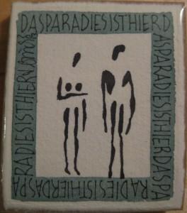 Das kleine Kunstwerk zeigt eine Strichzeichnung einer Frau und rechts neben ihr eines stilisierten, etwas größeren Mannes, rundherum steht auf blauem Grundgeschrieben: Das Paradies ist hier