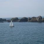 Blick aufs Meer in Rothéneuf, im Vordergrund ein weißes Segelboot, im Hintergrund eine Reihe großer, runder Felsen