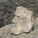 Ein aus dem Felsen herausgehauener übergroßer Steinkopf mit ausdrucksstarkem Gesichtsausdruck