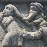 Ein Mann mit dem typischen bretonischen Hut zeiht seine Frau von hinten am Zopf und gibt ihr gleichzeitig einen Tritt in den Hintern