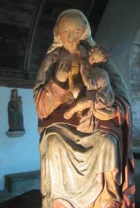 Marienstatue mit Jesuskind auf dem linken Arm, mit der rechten Hand holt die Gottesmutter ihre Brust aus dem Mieder
