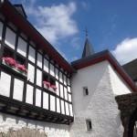 Links im Bild ein Fachwerkhaus mit Blumenkästen mit rosa Blümchen, rechts davon die Mauern der Kirche und der schieferbedeckte Kirchturm von St. Brigida