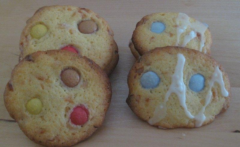 Kekse, die mit schwaren, roten und gelben Smarties oder mit blaune Smarties und weißem Zuckerguss dekoriert sind