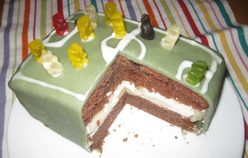 Die angeschnittene Torte, man sieht die Melonen-Joghurt-Schicht zwischen den Schokoböden