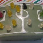 Eine rechteckige Torte, mit grünem Marzipanumhüllt, mit Zuckergusstreifen für die Linien und Gummibärchen als Fußballern.