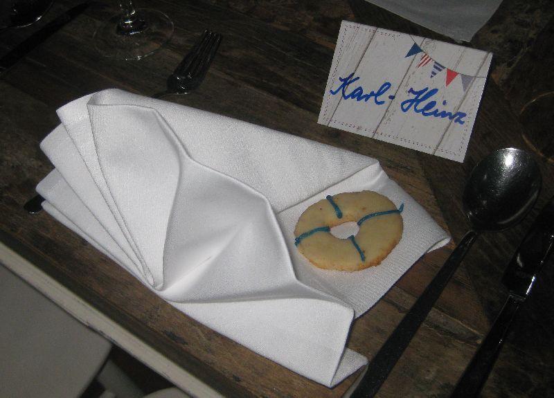 Eine als Muschel gefaltete weiße Serviette, auf der ein Keks in Gestalt eines Rettungsrings liegt