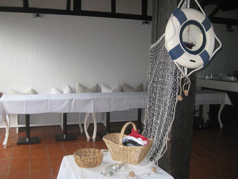 Kleiner Tisch mit maritimen Accessoires, daneben ein dunkler Holzbanken mit Rettungsring und Fischernetz