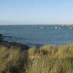 Blick auf die Bucht, im Vordergrund das Gras der Dünen, im Hintergrund einige große Felsen, dazwischen ein kleiner Naturhafen mit einigen kleinen Booten