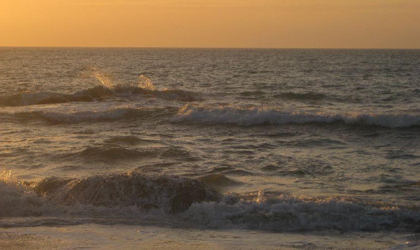 Hohe Wellen, die sich mit großem Spritzen an einem Felsen brechen im orangenen Licht des Sonnenuntergangs