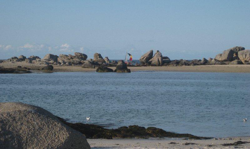 Blick in die Bucht, im Hintergrund fährt ein Segelboot an den großen, markanten Felsen vorbei