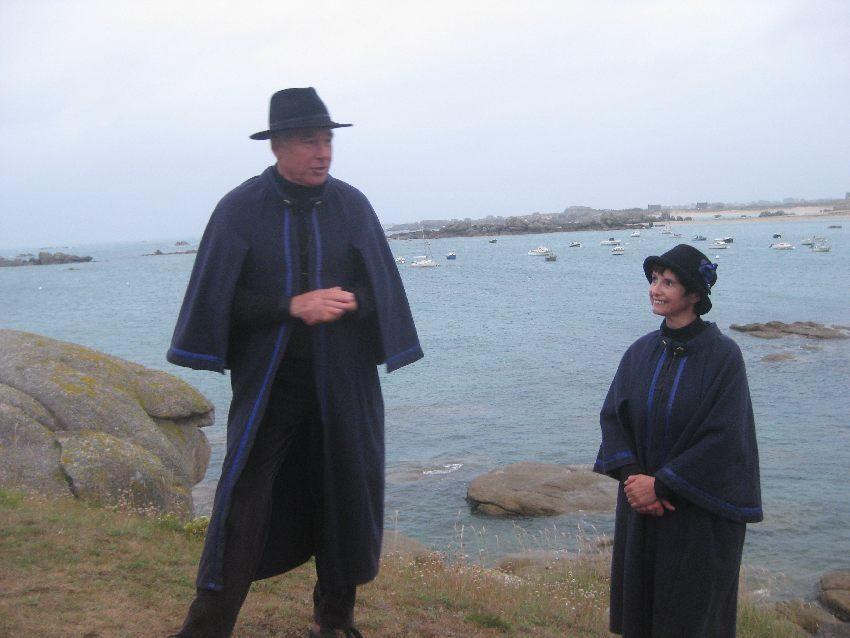 Joel und Marie-Pierre auf den Klippen vor Kerlouan, beide tragen dunkelblaue Mäntel und schwarze Hüte, die Kleidung der Conteurs