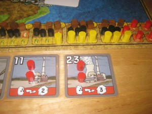 Zwei Kärtchen für Atomkraftwerke und der Teil des Spielplans, auf dem die Holzsteine für die Energierohstoffe von Funkenschlag stehen