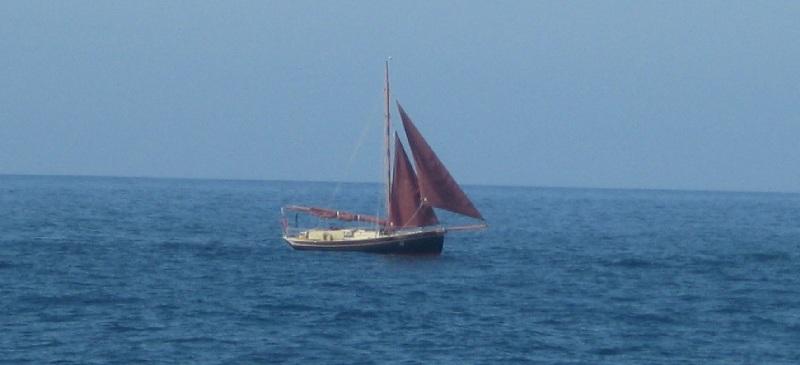 Ein Boot mit von Wind, Sand und Sonne braun gefärbten Segeln auf dem Wasser
