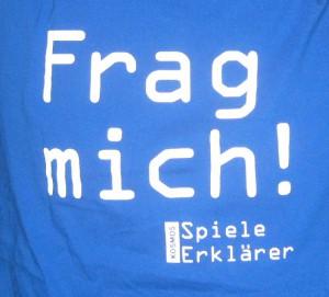 Rückenansicht eines Spieleerklärer-T-Shirts mit der Aufschrift: Frag mich! Kosmos Spiele Erklärer