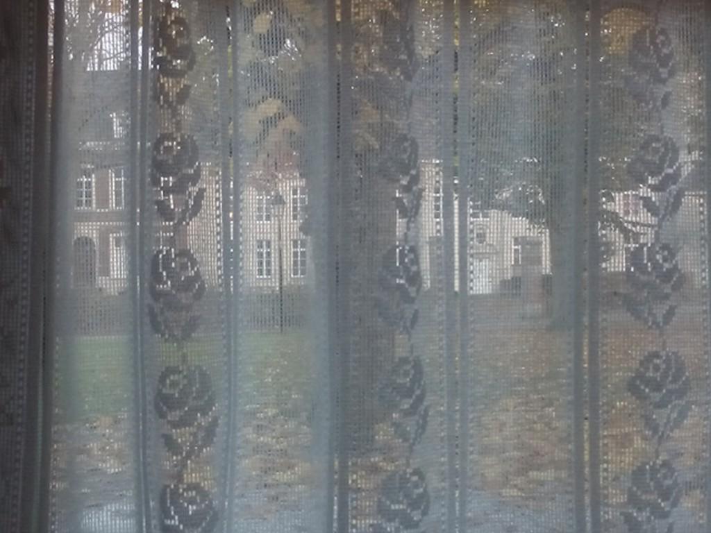 Blick auf das Benediktinerinnenkloster durch die Gardinen des gegenüberliegenden Cafés
