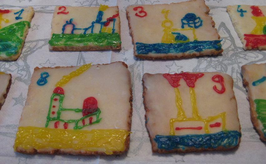 Vier Adventskalender-Kekse mit verschiedenen mit Zuckerschrift gemalten Kraftwerken