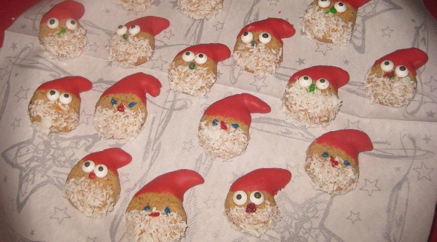 Kleine Mandelplätzchen it rot eingefärbtem Mützchen und Kokosflockenbart
