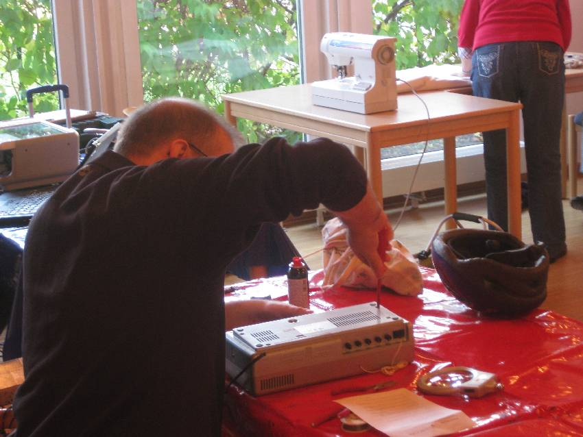 Ein Mann repariert ein Radiogerät.