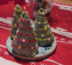 3 Lebkuchen in Kegelform, mit gefärbter Schokolage grün angestrichen und mit Zukerfarbe und bunten Streuseln als Tannenbäumchen verziert
