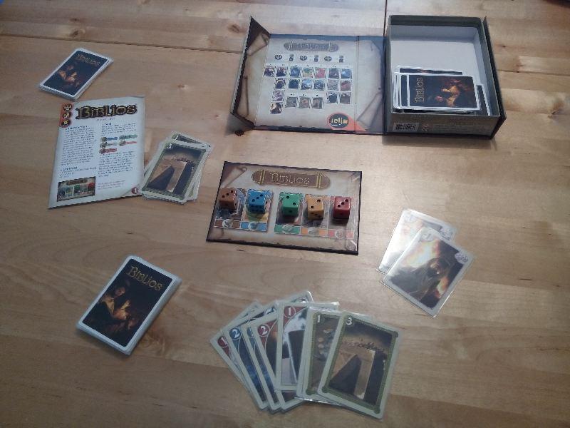 Die verschiedenen Elemente des Spiels Biblios: Karten, Würfel und eine Übersichtskarte