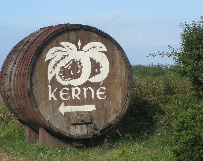 Cidrefass mit dem Logo der Cidrerie Kerné als Wegweiser am Straßenrand