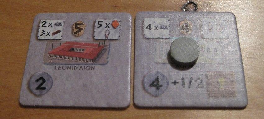 Zwei Stadterweiterungskärtchen, eines wurde auf Kredit gekauft und hat daher eine Münze in die Mitte gelegt bekommen