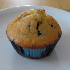 Blaubeermuffin in einem blauen Förmchen auf einem Teller