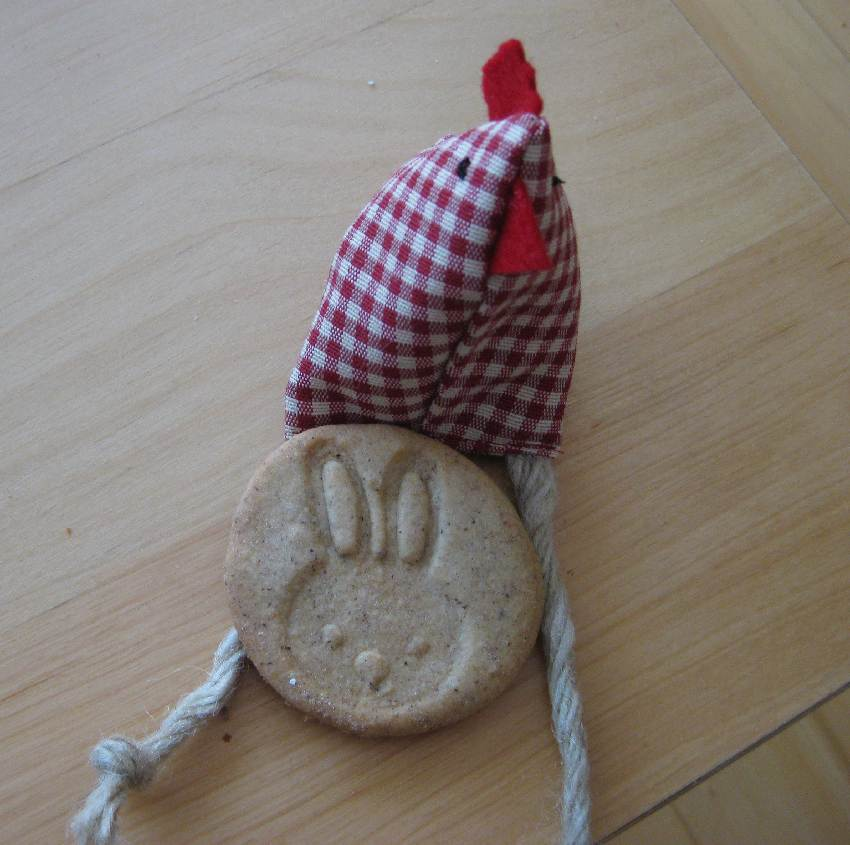Keks mit einem Osterhasenstempel dekoriert vor einem Stoffhühnchen