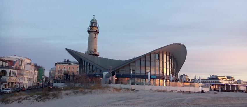 """Historischer Leuchtturm von Warnemünde mit dem modernen geschwungenen Dach des """"Teepotts"""""""
