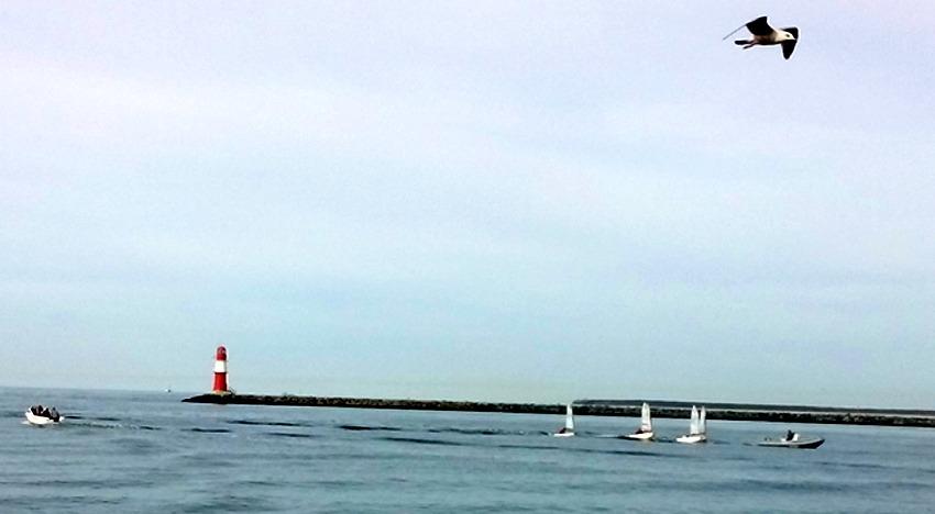 Roter Leuchtturm am Ende der Mole mit kleinen Segelbooten eines Kindersegelkurses