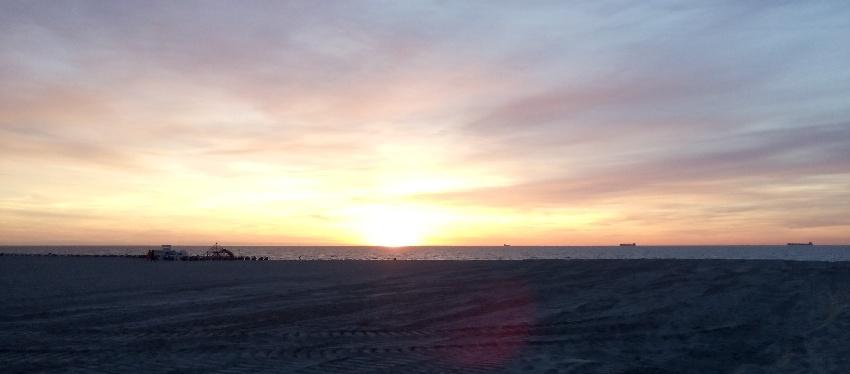 Der Sonnenuntergang am Ostseestrand färbt den Himmel in allen Farben von orange bis lila